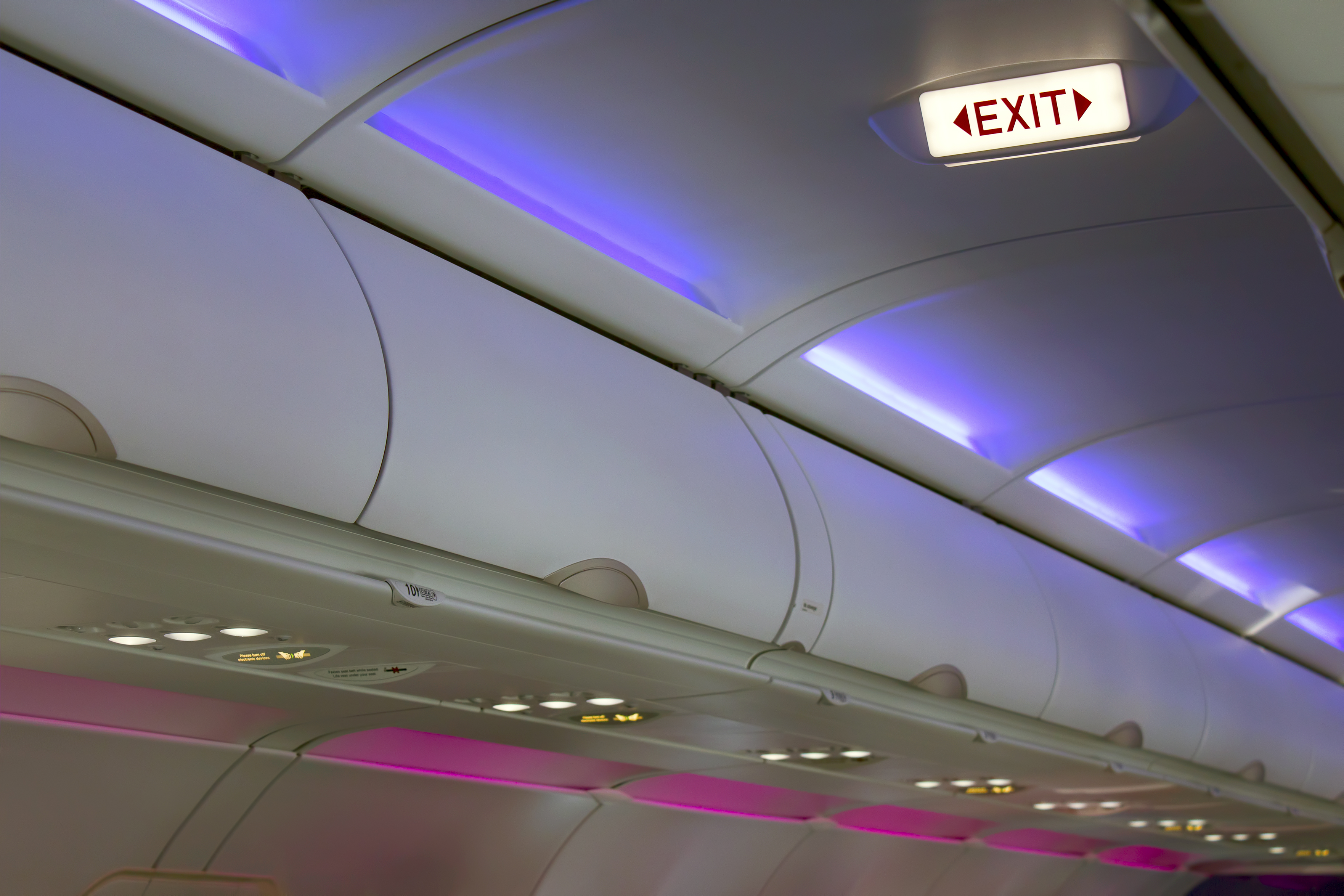 picture of interior cabin lighting, including blue ceiling lights, purple wall lights and passenger service module reading lights
